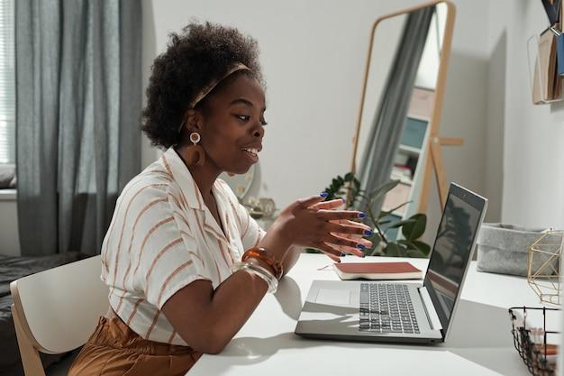 화상 채팅에서 의사 소통하는 젊은 아프리카 여성 프리랜서