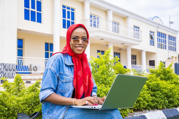 公園で彼女のラップトップで作業しながら笑っている若いアフリカの女性