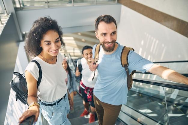 배경에 인도 남성 동안 배낭 이동 계단에 서 유럽 남자와 젊은 아프리카 여성