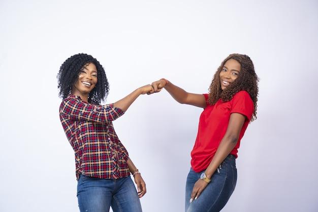 Giovani femmine africane fist-bumping - concetto di supporto