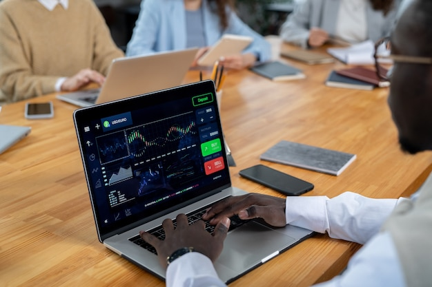 財務データを扱う作業中にラップトップの前に座っている若いアフリカの金融業者