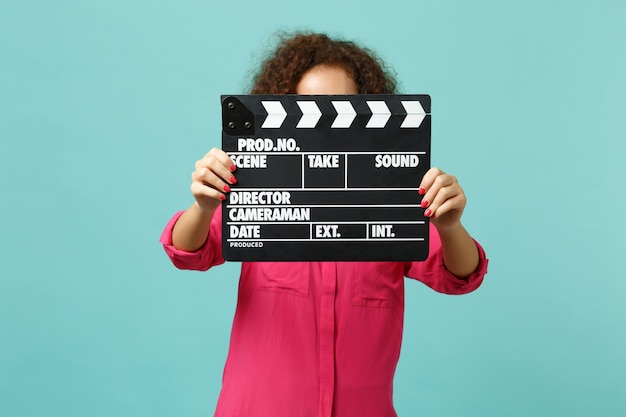 Young african girl in casual clothes covering face with classic black film making clapperboard isolated on blue turquoise background. people sincere emotions, lifestyle concept. mock up copy space.