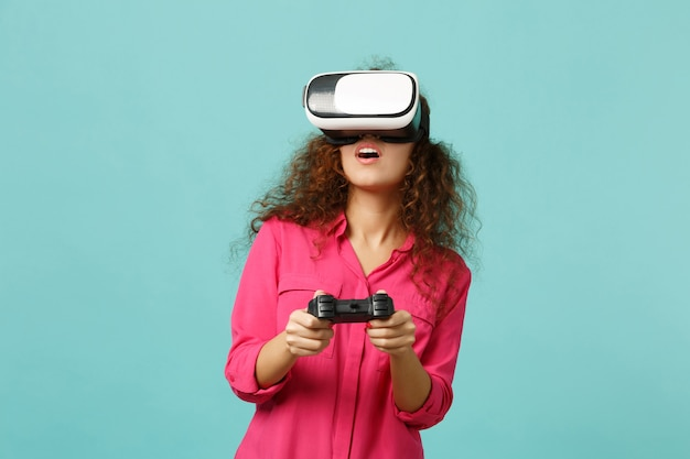 Giovane ragazza africana in abiti casual guardando in cuffia, giocando al videogioco con joystick isolato su sfondo blu turchese parete. persone sincere emozioni, concetto di stile di vita. mock up copia spazio.