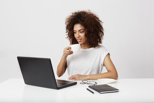 白い壁に笑みを浮かべてラップトップを見てカップを保持している若いアフリカの女の子。
