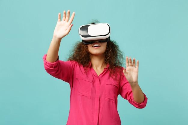 Giovane ragazza africana che guarda in cuffia, tocca qualcosa come premere clic sul pulsante, indicando lo schermo virtuale galleggiante isolato su sfondo blu turchese. persone sincere emozioni, concetto di stile di vita.