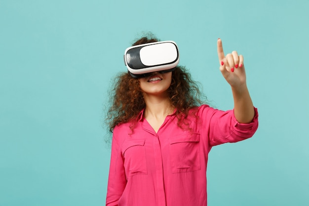 Young african girl looking in headset, touch something like push click on button, pointing at floating virtual screen isolated on blue turquoise background. people sincere emotions, lifestyle concept.