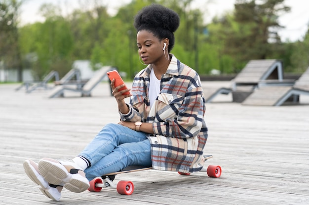 Young african girl sit on longboard with smartphone in hand text outdoor in park using g connection