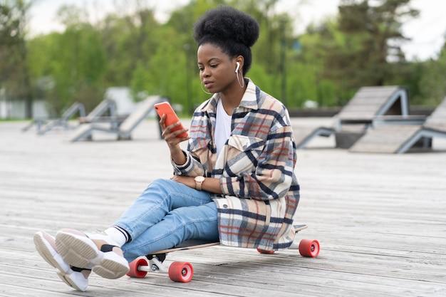젊은 아프리카 소녀는 g 연결을 사용하여 야외 공원에서 스마트폰을 들고 롱보드에 앉아 있습니다.