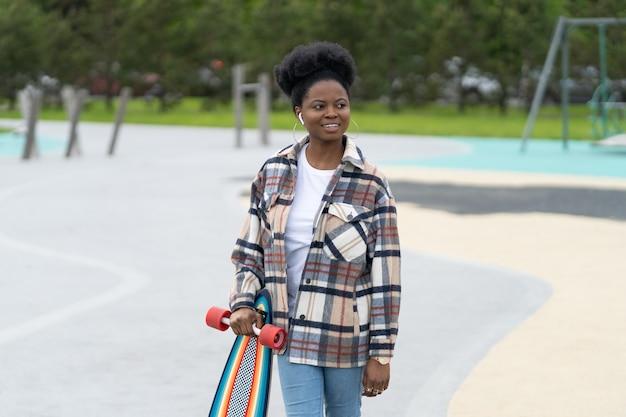 젊은 아프리카 소녀 스케이팅 스케이트 공원에서 캐주얼 옷을 입고 스케이트 공원 도시 여성에서 롱보드를 들고