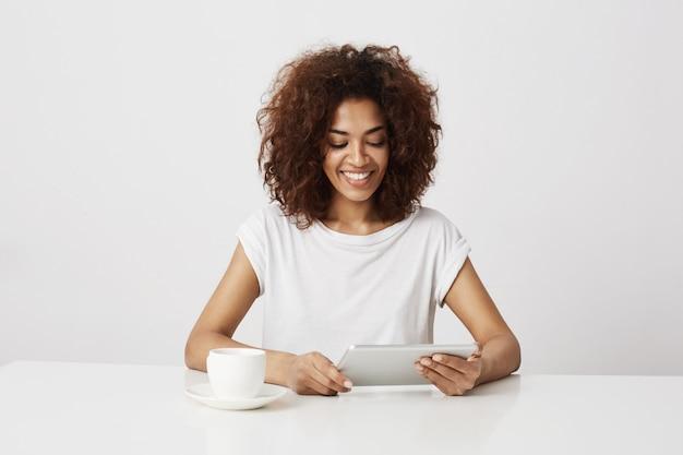 白い壁にタブレットを見て笑っている若いアフリカの女の子。コピースペース。