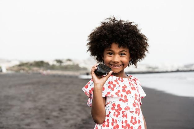 해변에서 야외에서 웃 고 젊은 아프리카 소녀-얼굴에 초점