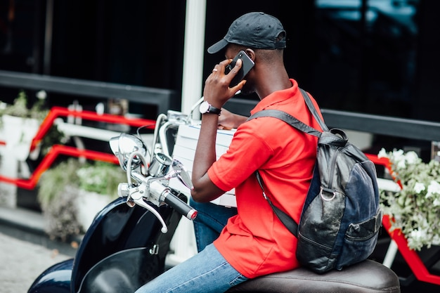 Young african guy accepts the order by phone and write in motorbike holding boxes with pizza