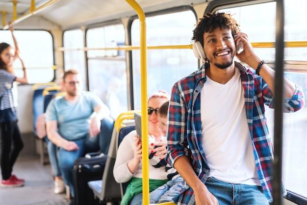 대 중 교통을 타고있는 동안 음악을 듣고 젊은 아프리카 남자.