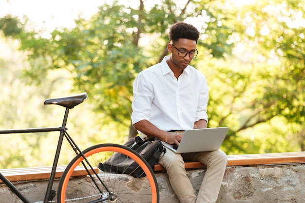Young african handsome man using laptop computer.