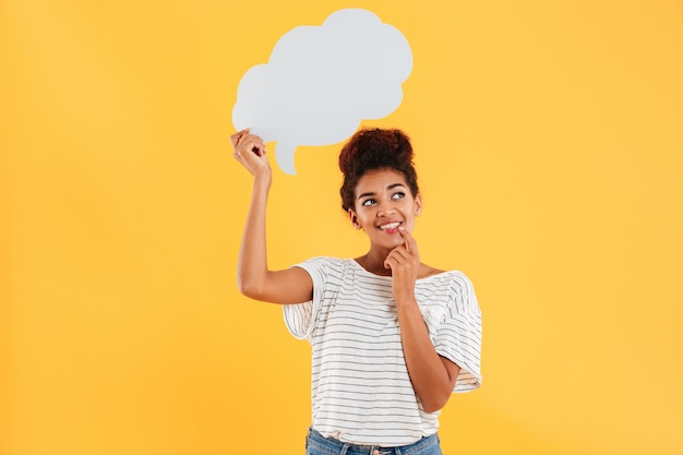 Young african happy thoughtful lady looking up and holding blank speech bubble isolated over yellow