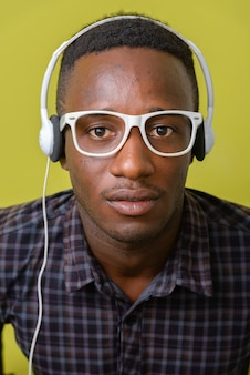 Young african hipster man isolated against yellow space