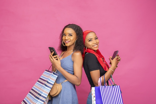 Молодые африканские дамы просматривают что-то на своих мобильных телефонах, неся сумки с покупками
