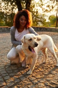 Giovane signora africana in abbigliamento casual che si siede e che abbraccia cane nel parco