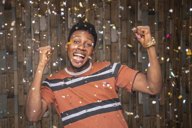 Young african male celebrating with confetti floating around