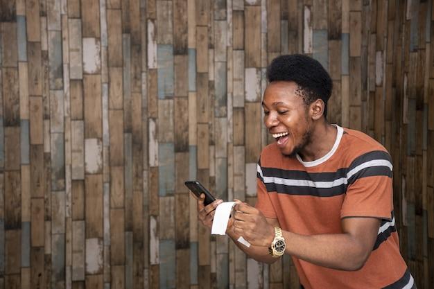 Giovane maschio africano che si sente eccitato mentre tiene il suo smartphone e un foglio di carta