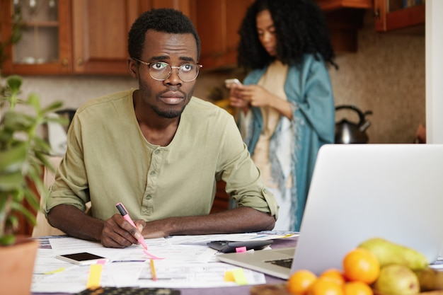 Молодой африканский мужчина испытывает стресс, когда оплачивает счета онлайн, подсчитывает расходы на газ и электричество, сидит за кухонным столом перед открытым ноутбуком и делает заметки. финансовый стресс и долги