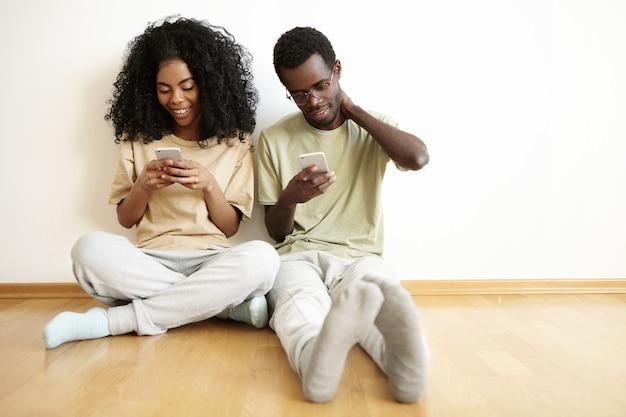 Giovane maschio e femmina africani che utilizzano il wi-fi gratuito a casa, seduti sul pavimento di legno uno accanto all'altro: amici di messaggistica donna online tramite social network