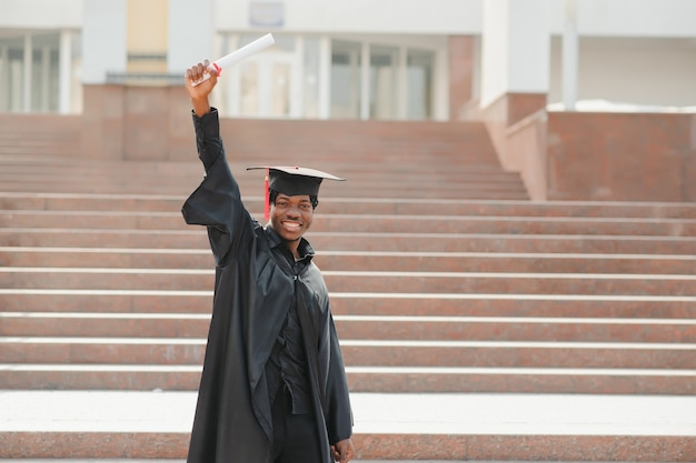 Молодой африканский выпускник мужского пола стоит перед зданием университета