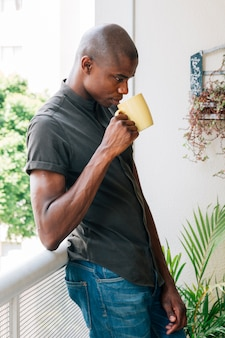 Young african male leaning on the railing of balcony drinking the coffee