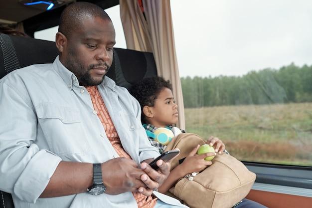 Молодой африканский пассажир-мужчина, прокручивающий в смартфоне