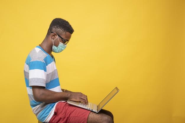 彼のラップトップで作業中に眼鏡とフェイスマスクを身に着けている若いアフリカの男性-covid-19