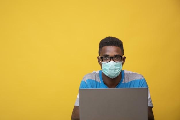 Giovane maschio africano che indossa occhiali e una maschera facciale mentre lavora al suo laptop - covid-19