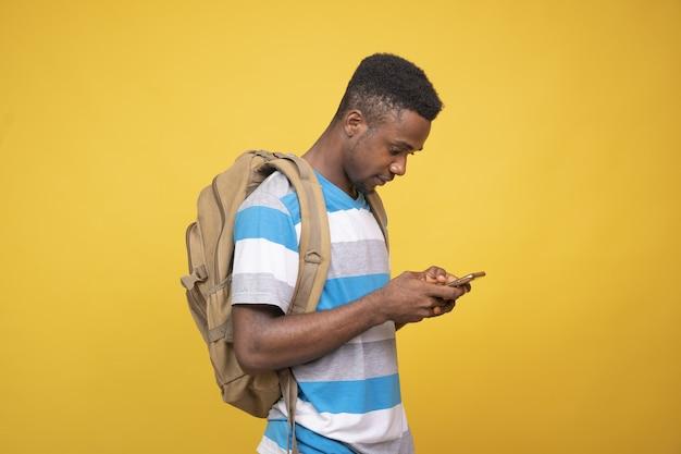 黄色の壁に彼の電話を使用してバックパックを持つ若いアフリカの男性