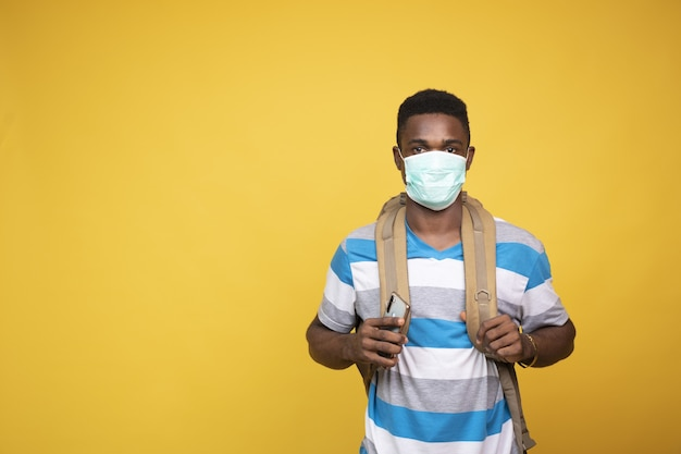 Young african male with a backpack wearing a facemask - covid-19