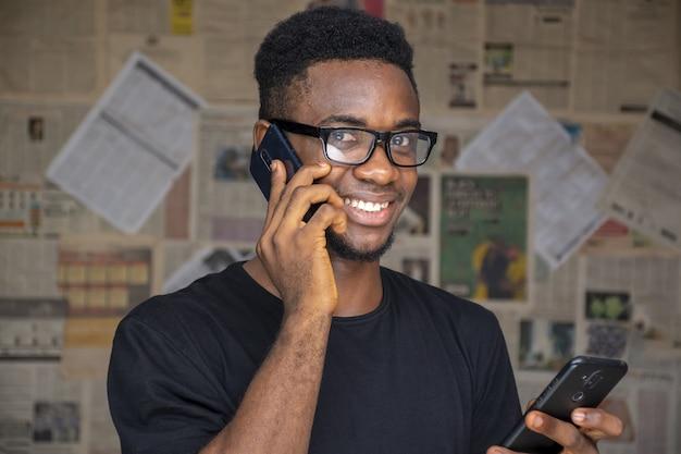 방에서 다른 안경을 사용하면서 안경을 쓴 젊은 아프리카 남성