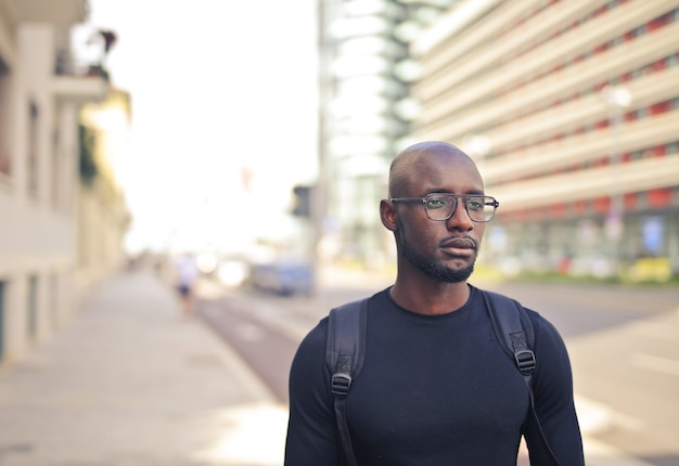 通りで黒いtシャツとバックパックを身に着けている眼鏡をかけた若いアフリカ人男性