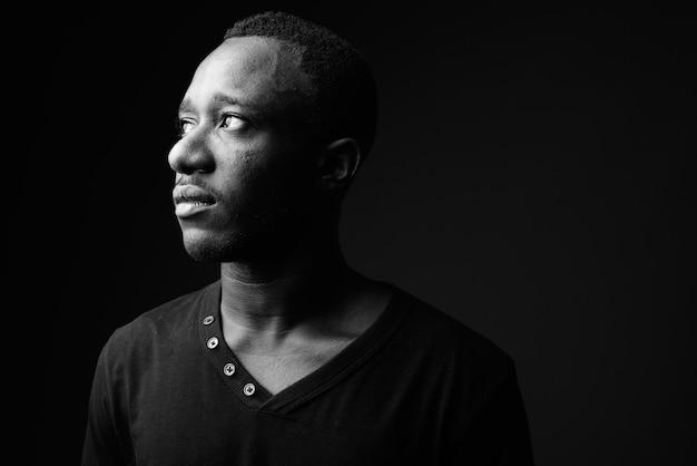 Молодой африканец против черной стены в черно-белом