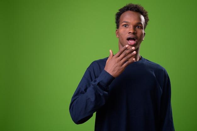 Молодой африканский человек против зеленой стены