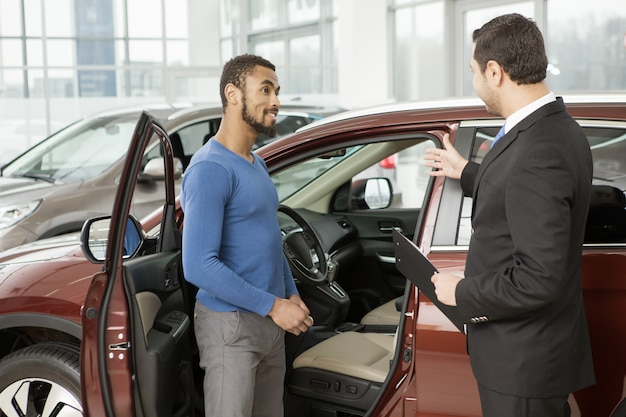 Young african man buying a car from a professional salesman