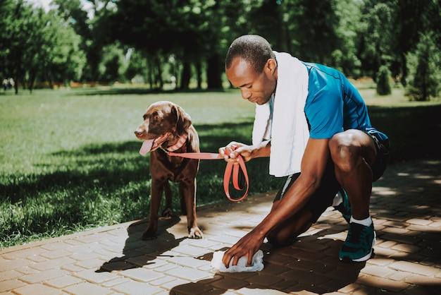 若いアフリカ人は犬の後をクリーンアップします。