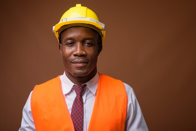 Young african man construction worker against brown background