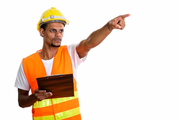 Young african man construction worker holding clipboard while pointing at distance