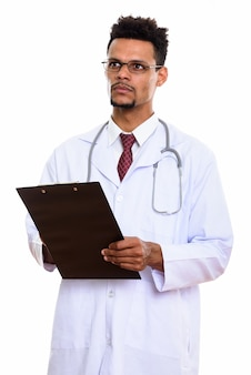 Young african man doctor holding clipboard while thinking