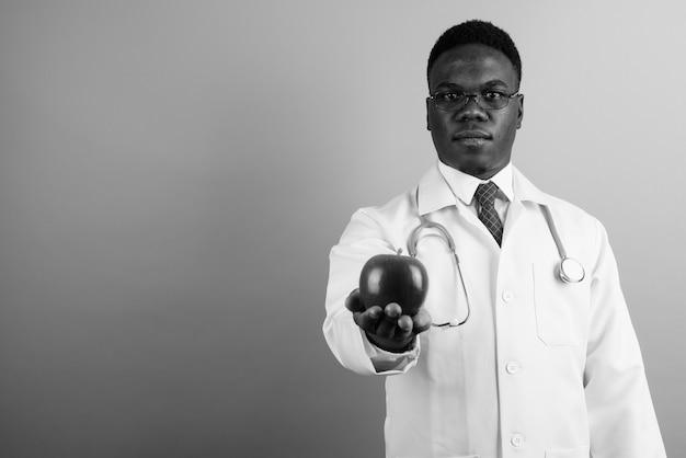 Молодой африканский человек-врач в очках на белой стене. черное и белое