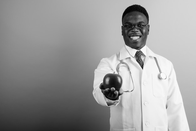 Young african man doctor wearing eyeglasses against white wall. black and white