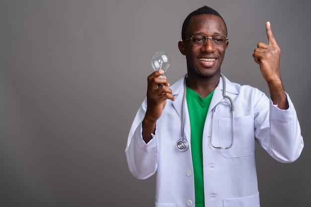 Young african man doctor wearing eyeglasses on gray wall