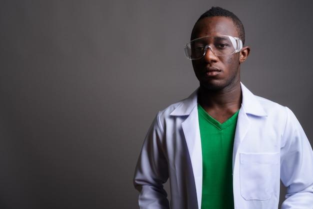 灰色の壁に保護眼鏡をかけている若いアフリカ人医師