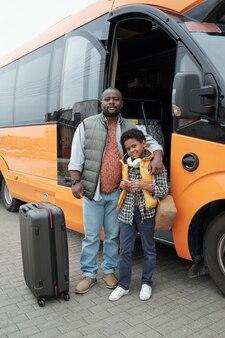 Молодой африканский мужчина обнимает своего милого сына на вокзале