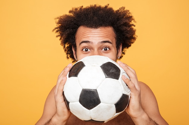 Young african man hiding face behind a foot ball