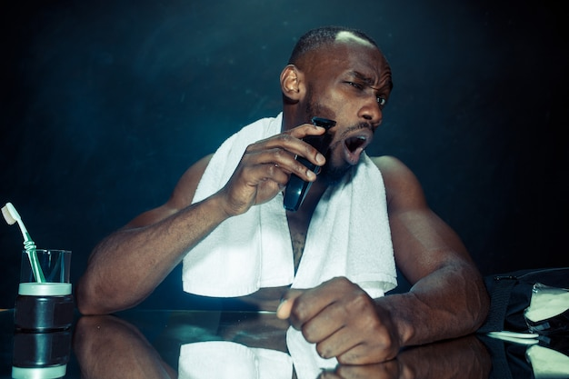 自宅で彼のひげを引っ掻く鏡の前に座っている寝室の若いアフリカ人。人間の感情の概念