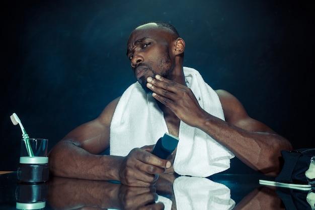 Молодой африканец в спальне, сидя перед зеркалом, почесывая бороду дома. концепция человеческих эмоций